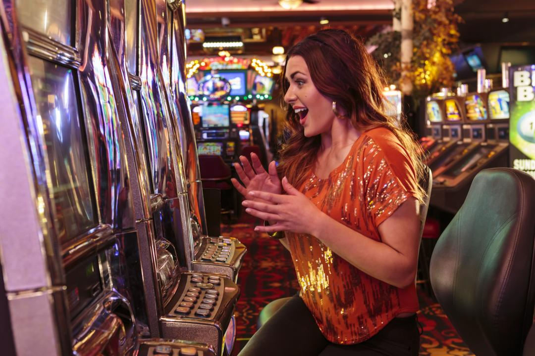 Young woman gambling at slots