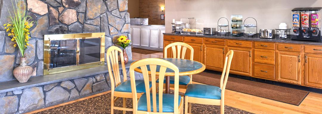 Lobby breakfast area with fireplace, dining table, and breakfast counter