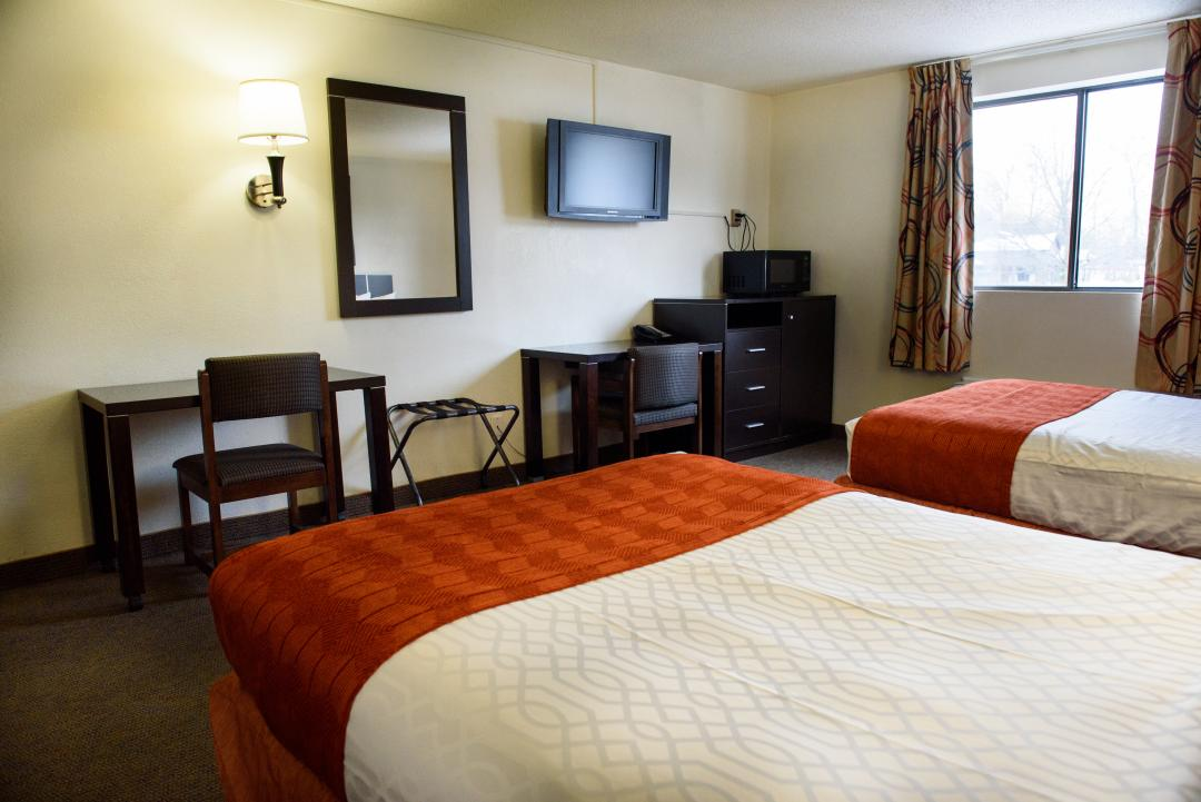 Two double beds with mounted TV and other amenities