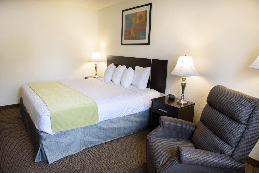 Guest room with one king bed, nightstands and armchair