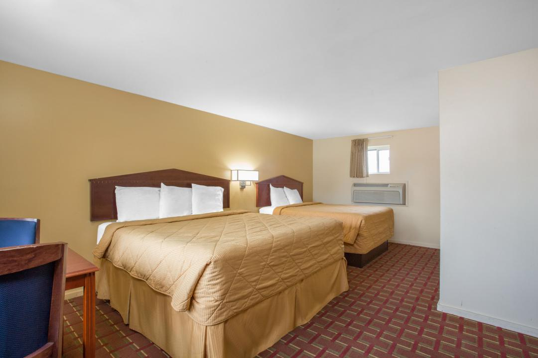 Guestroom with two queen beds, air conditioning and dining area for two