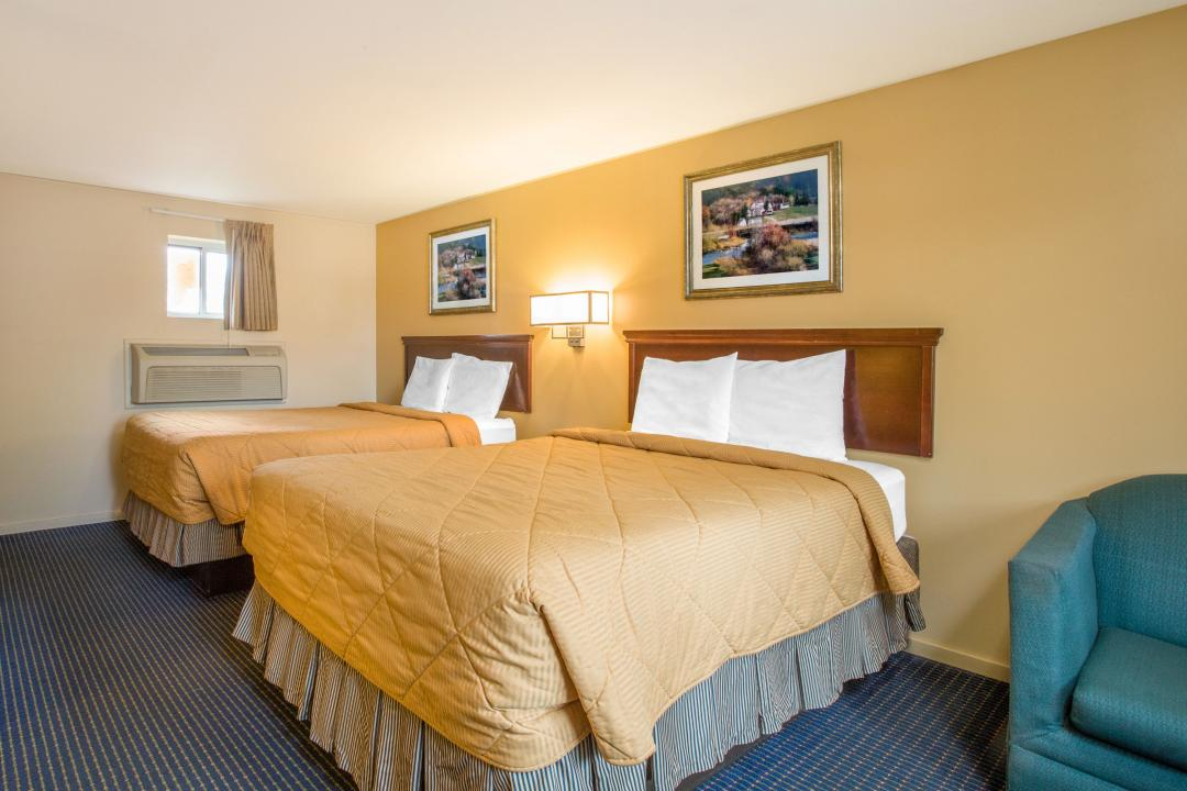 Two queen guest room with air conditioning and armchair