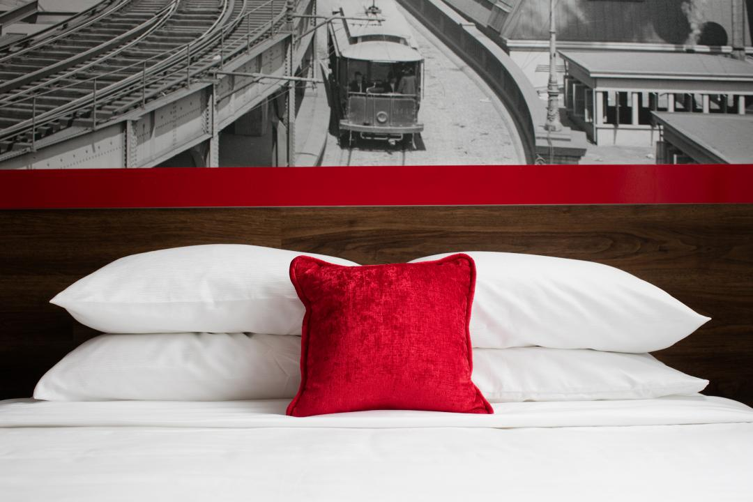 Signature Bed with Red Pillows
