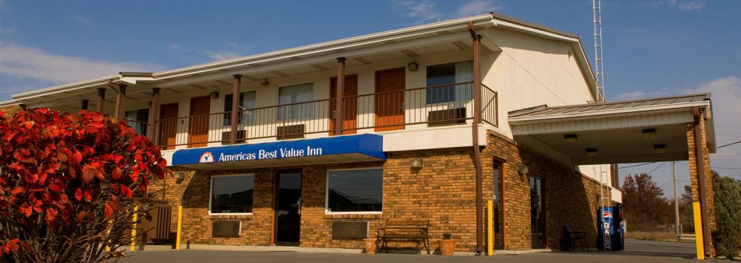 View of hotel lobby entrance and blue awning and bench