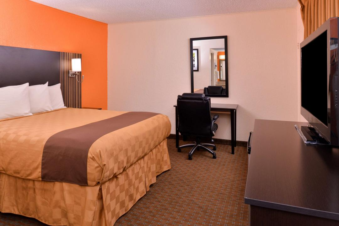 Spacious Queen guest room with desk and flatscreen TV