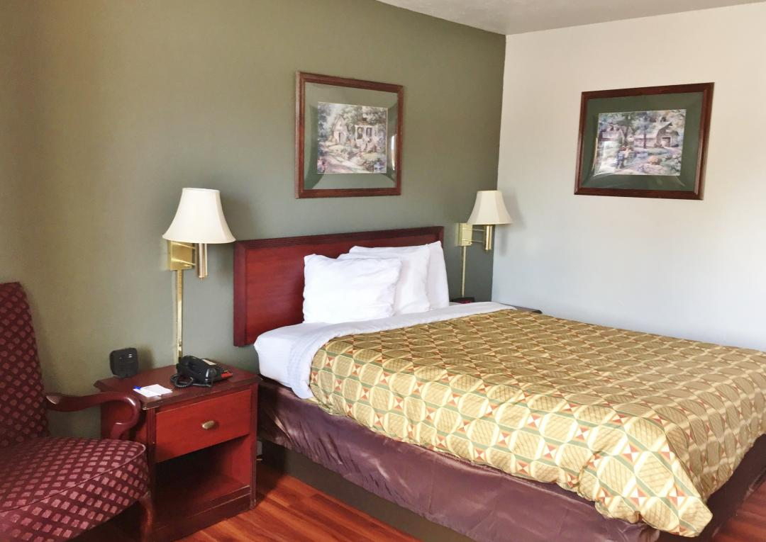Comfortable guest room with one queen bed and chair