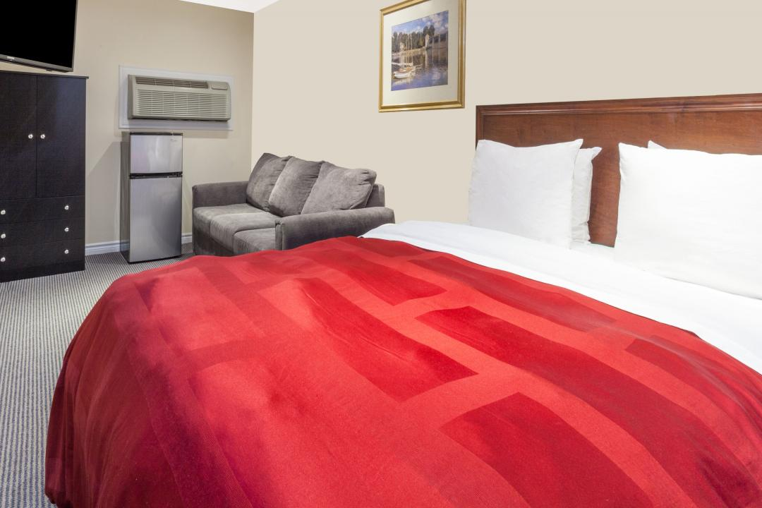 Guestroom with queen bed, flatscreen TV, refrigerator, air conditioning and sofa