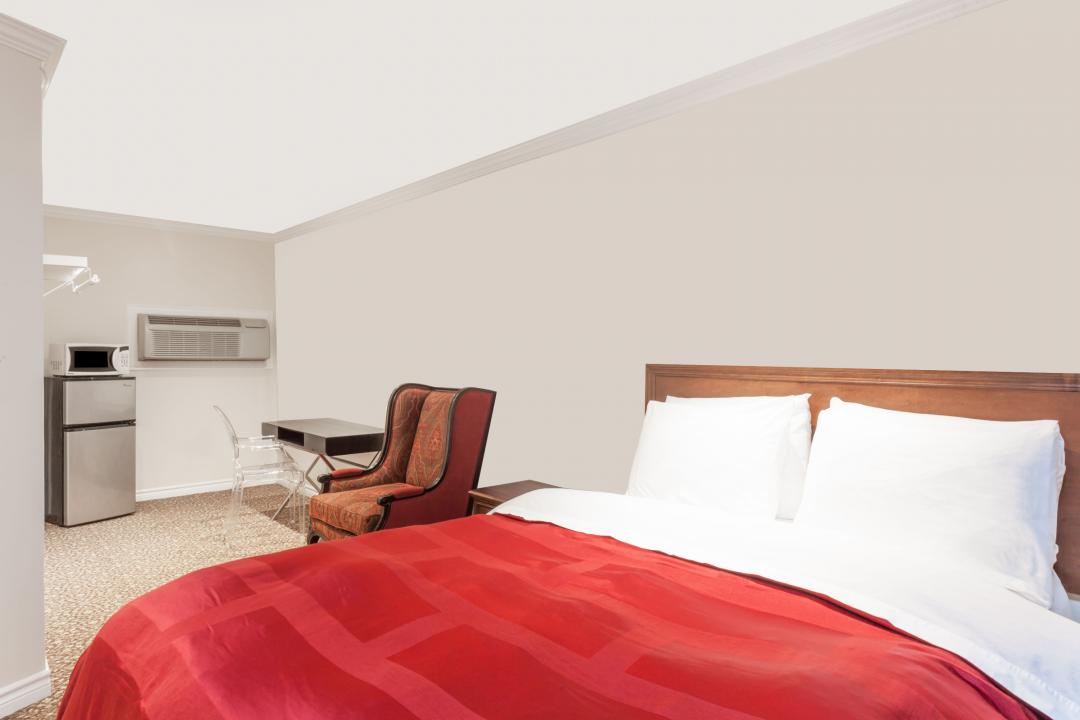 Guestroom with queen bed, refrigerator, microwave, air conditioning, desk and armchair