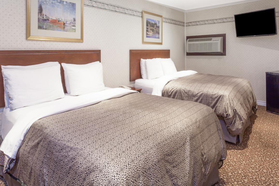 Guestroom with two queen beds, flatscreen TV, air conditioning, refrigerator