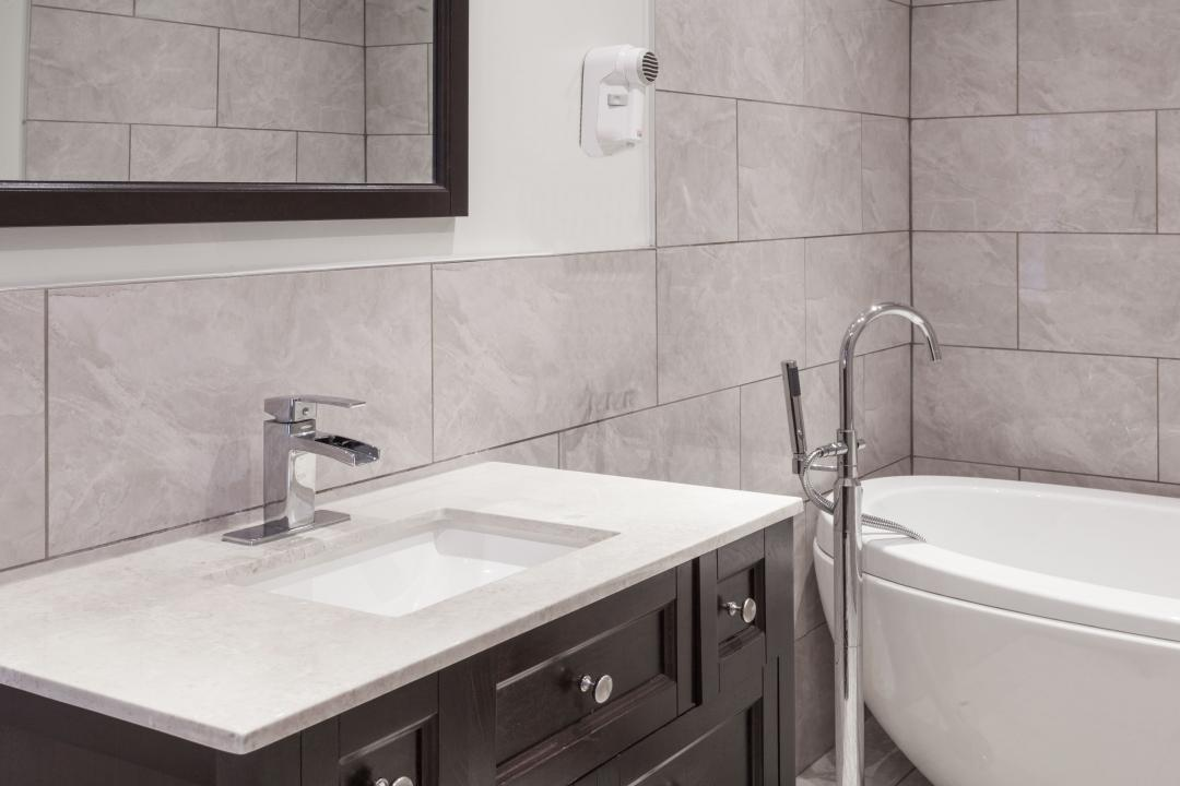 Guest bathroom with modern tub, marble vanity, tiled walls and hairdryer