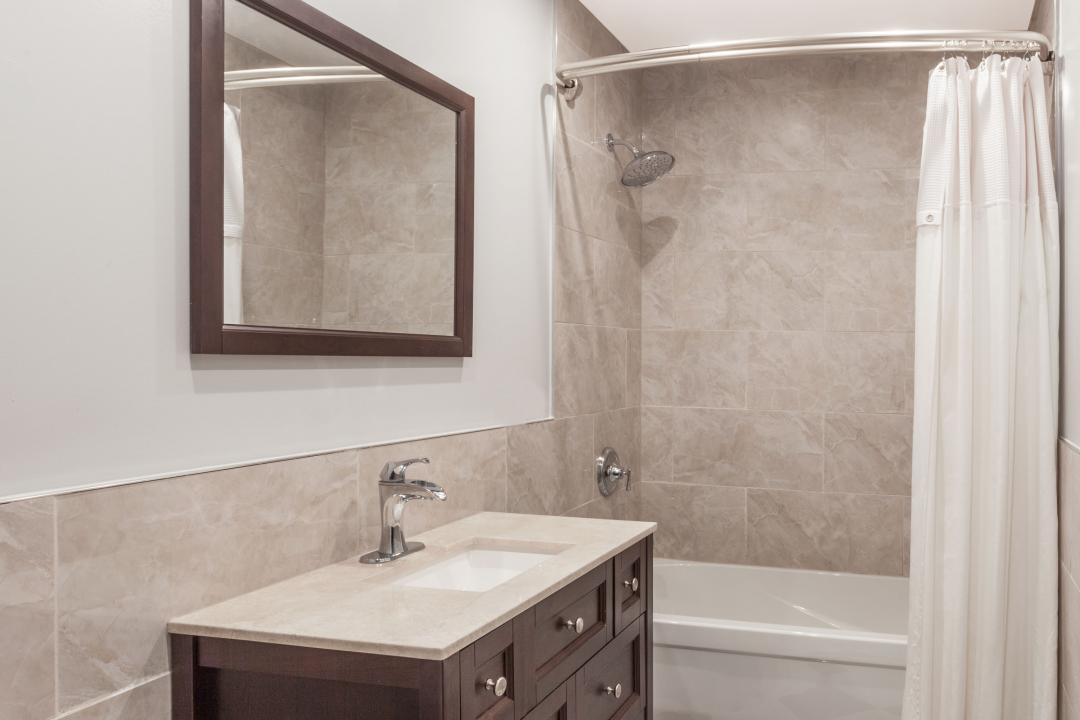 Guest bathroom with shower and tub combo, marble vanity and tiled walls