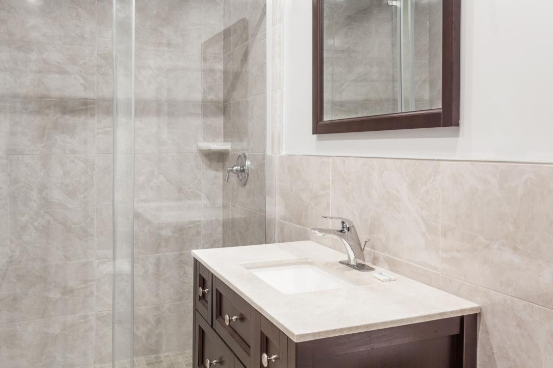 Clean and modern guest bathroom with tiled shower, walls and marble vanity