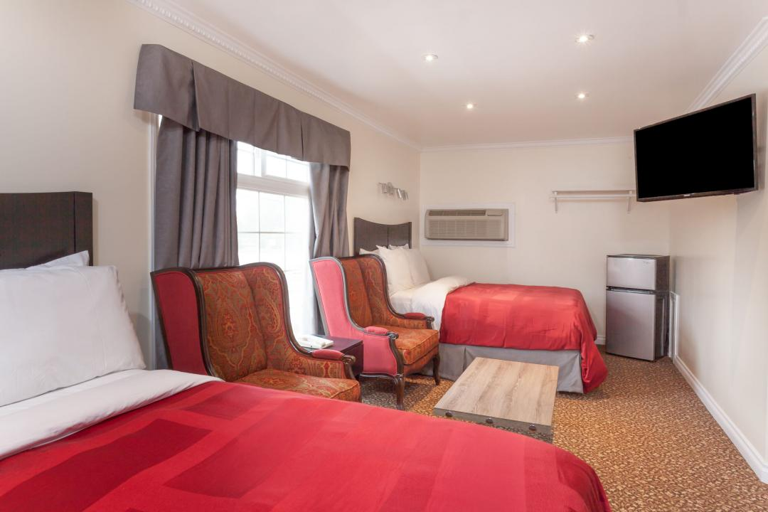 Guestroom with two queen beds, seating area with two armchairs, flatscreen TV and refrigerator
