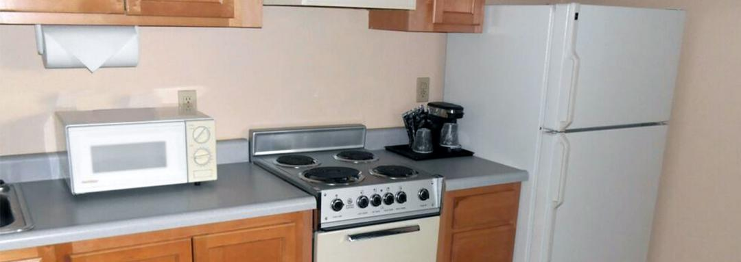 Guest bedroom kitchenette with stove microwave and refrigerator
