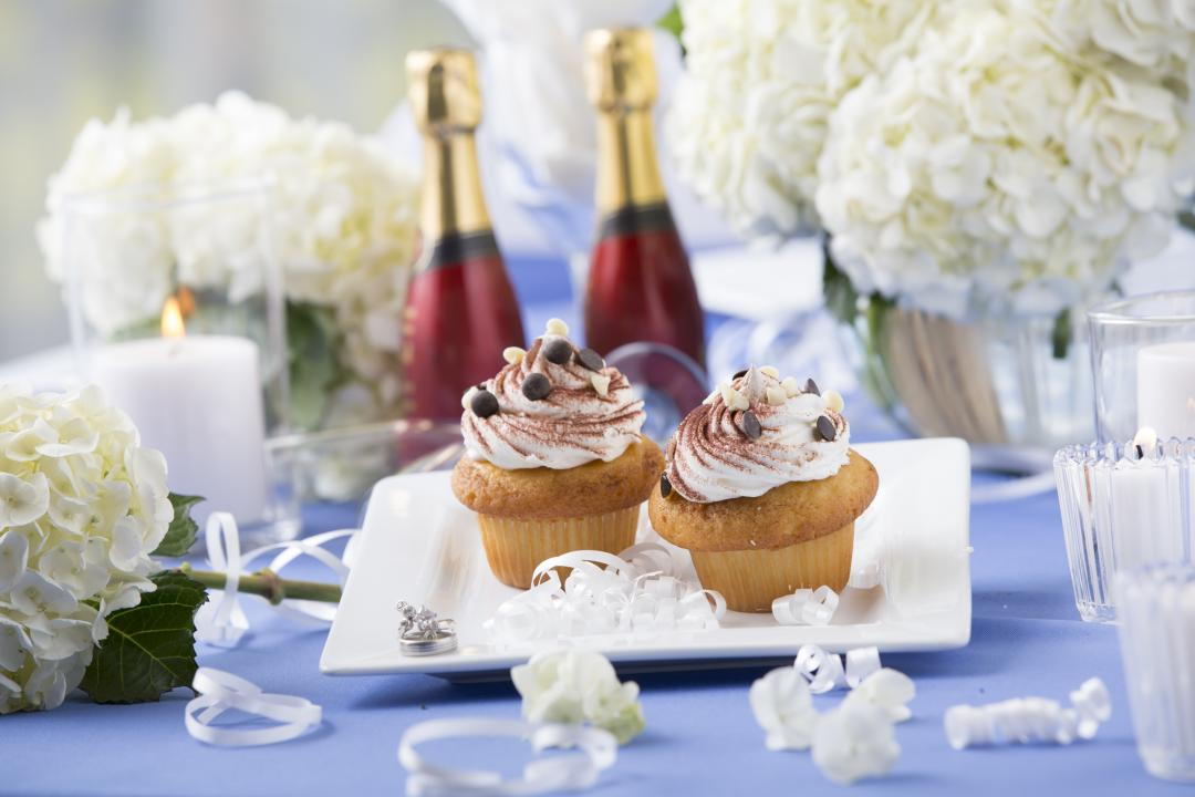 Cupcakes on a plate with wedding rings champaigne and confetti