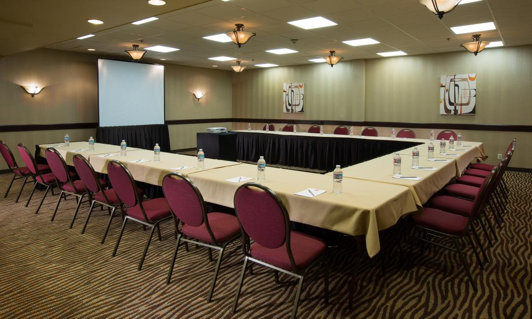 U-shaped meeting set up with water bottles and notepads