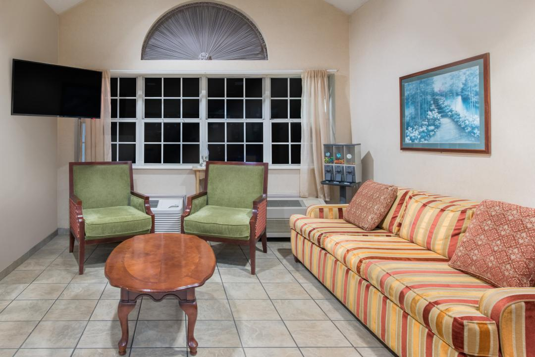 A sofa, two armchairs, a coffee table and flatscreen TV are included in the lobby guest seating area