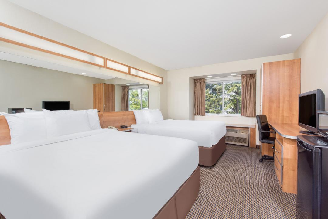 Clean guestroom with two queen beds, flatscreen TV, desk, microwave and refrigerator