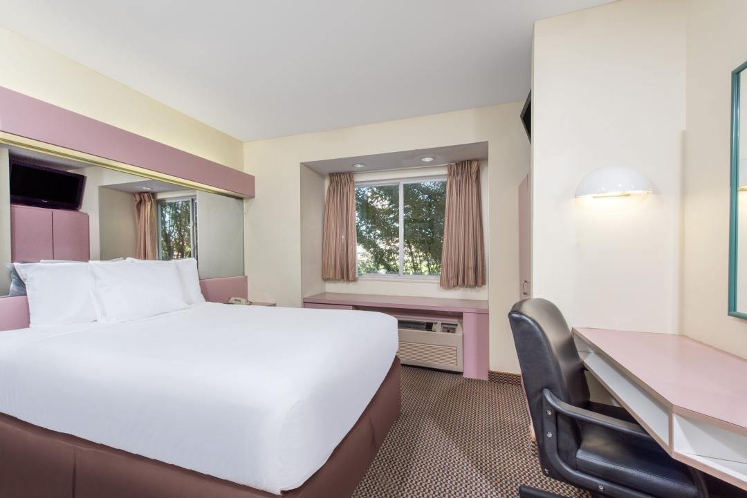 Clean guestroom with one king bed, desk and air conditioning