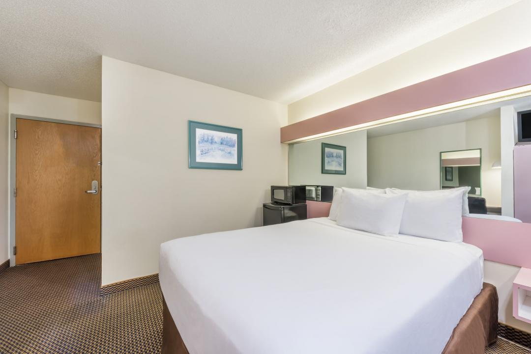 Alternate view of clean guestroom with one king bed showing microwave and refrigerator