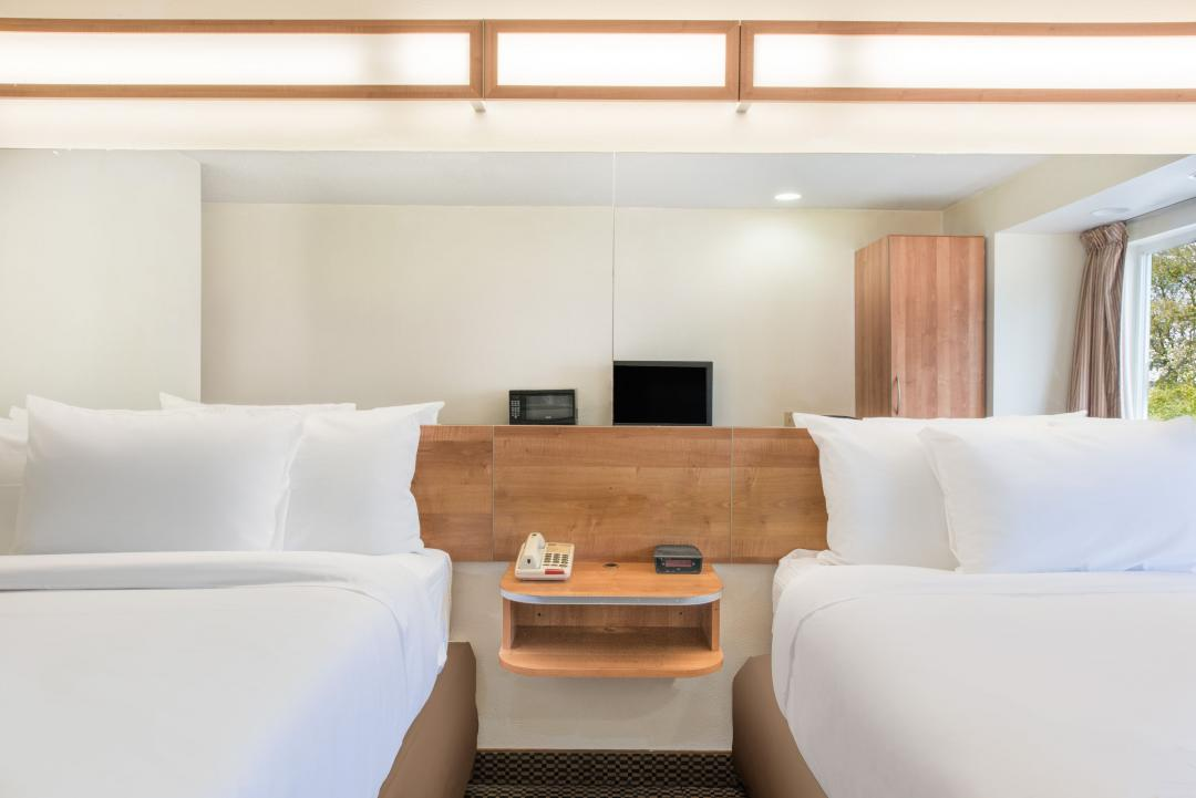 Clean two double bed guestroom with crisp white sheets