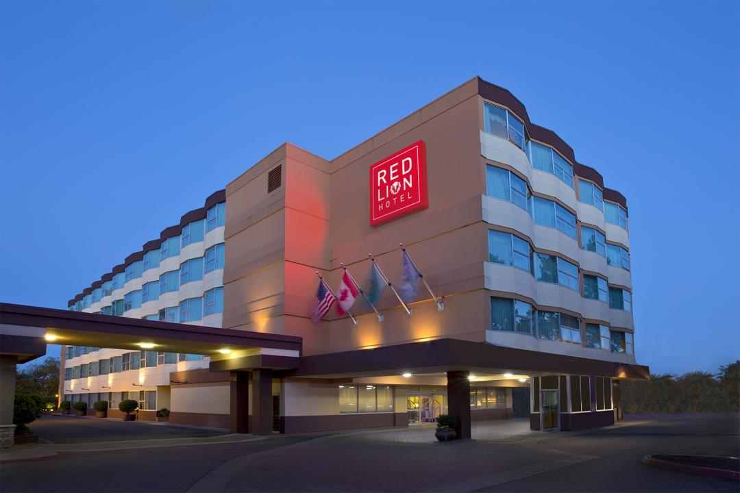 Hotel exterior at dusk with entrance to lobby, flags, and red sign