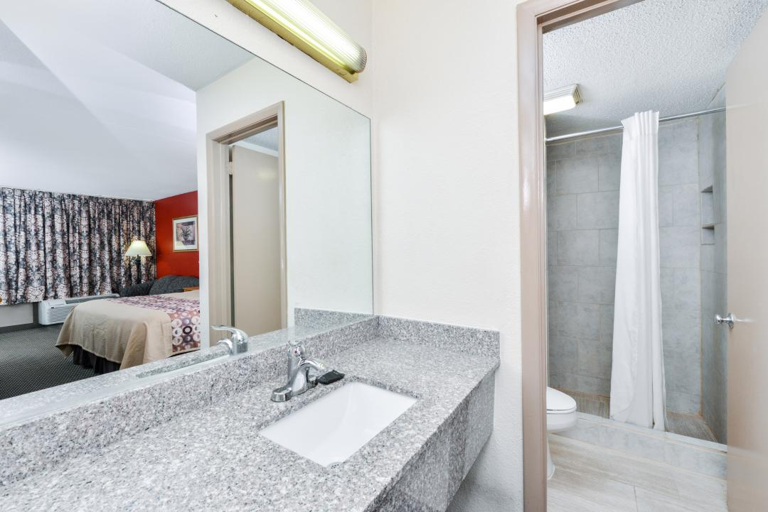 Clean, well lit guest room sink and walk-in shower