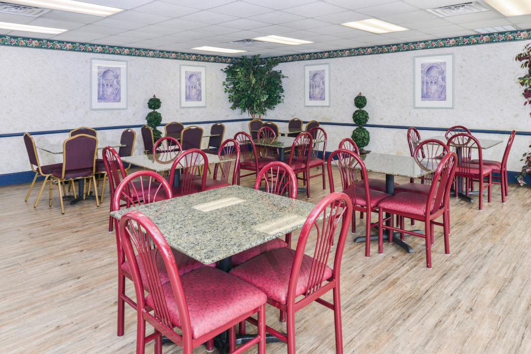Dining room with red chairs, potted plants