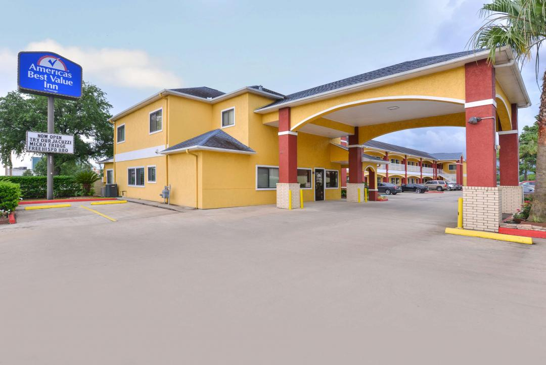 Hotel exterior with parking and sign