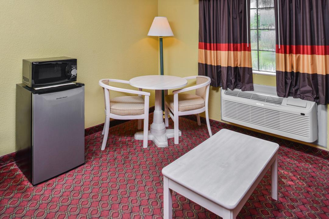 Guest room with table, chair, coffee table, fridge and microwave