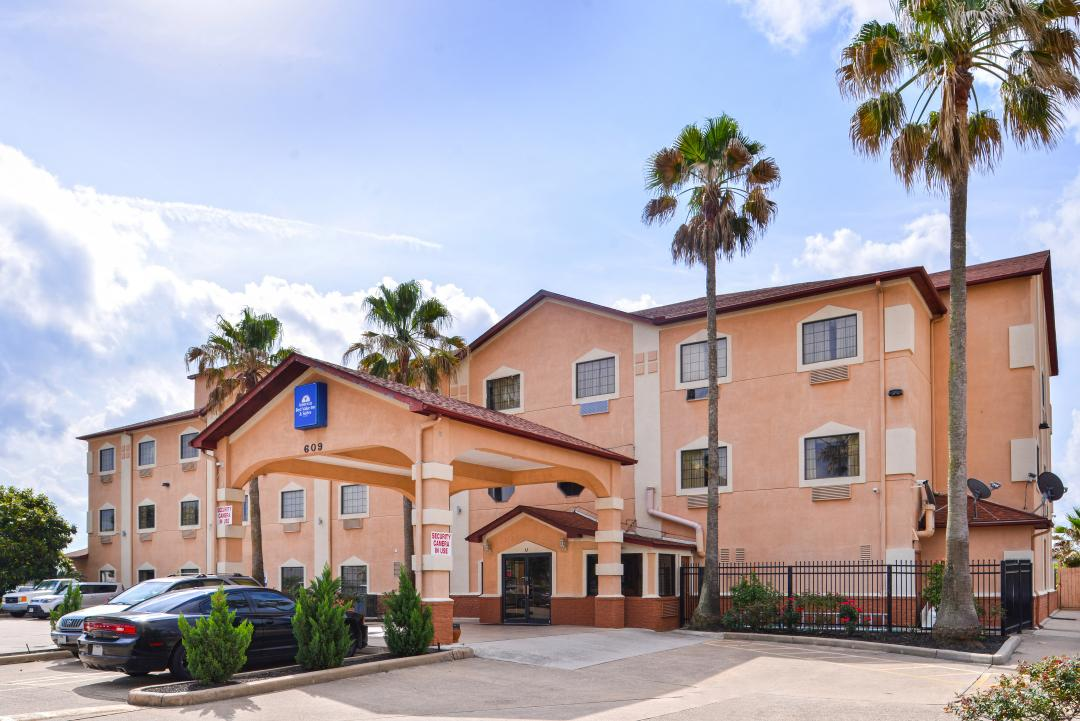 Hotel front exterior with parking and palm trees on a sunny day