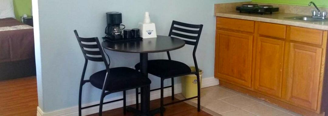 Guestroom dining table with two chairs and kitchenette sink