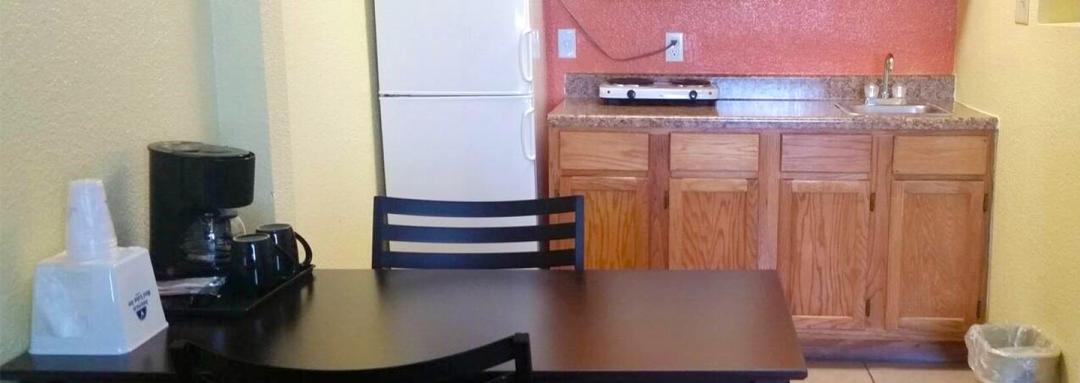 In-room kitchen area with refrigerator, sink, coffeemaker, stove, table and chairs