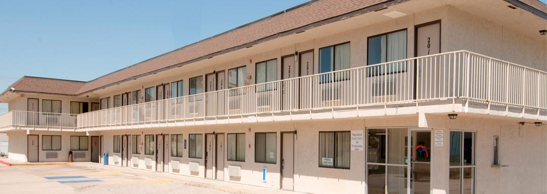Two story hotel exterior with parking lot