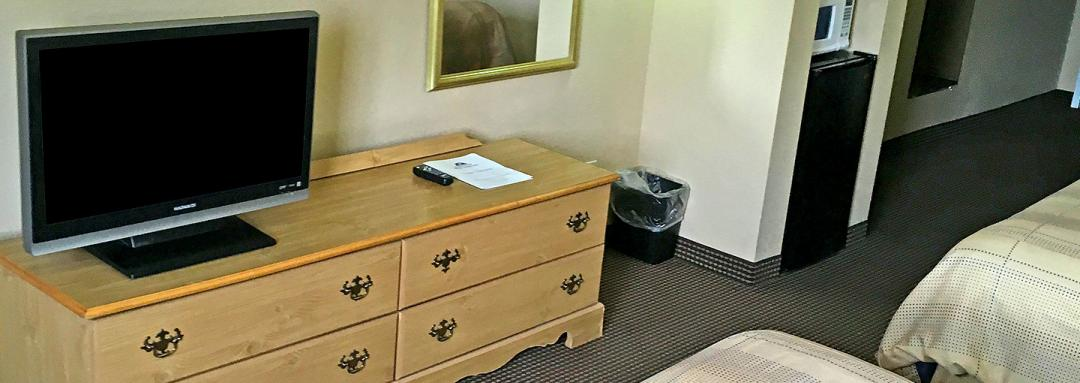 In-room TV with wooden dresser and partials beds