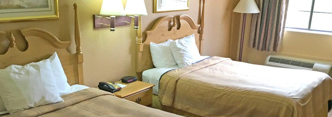 Two double beds guestroom with lamps and window