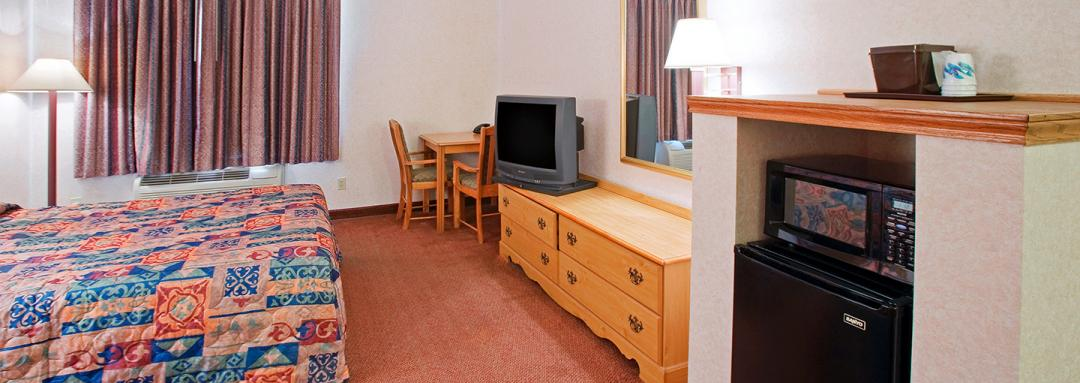One queen guestroom with microwave, mini-fridge, TV, and wooden dresser