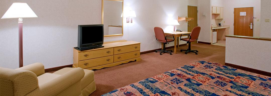 In-room amenities TV, arm chair, table with chairs, and kitchenette
