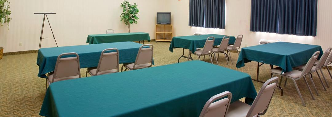 Meeting room with long tables, chairs, and green table cloths