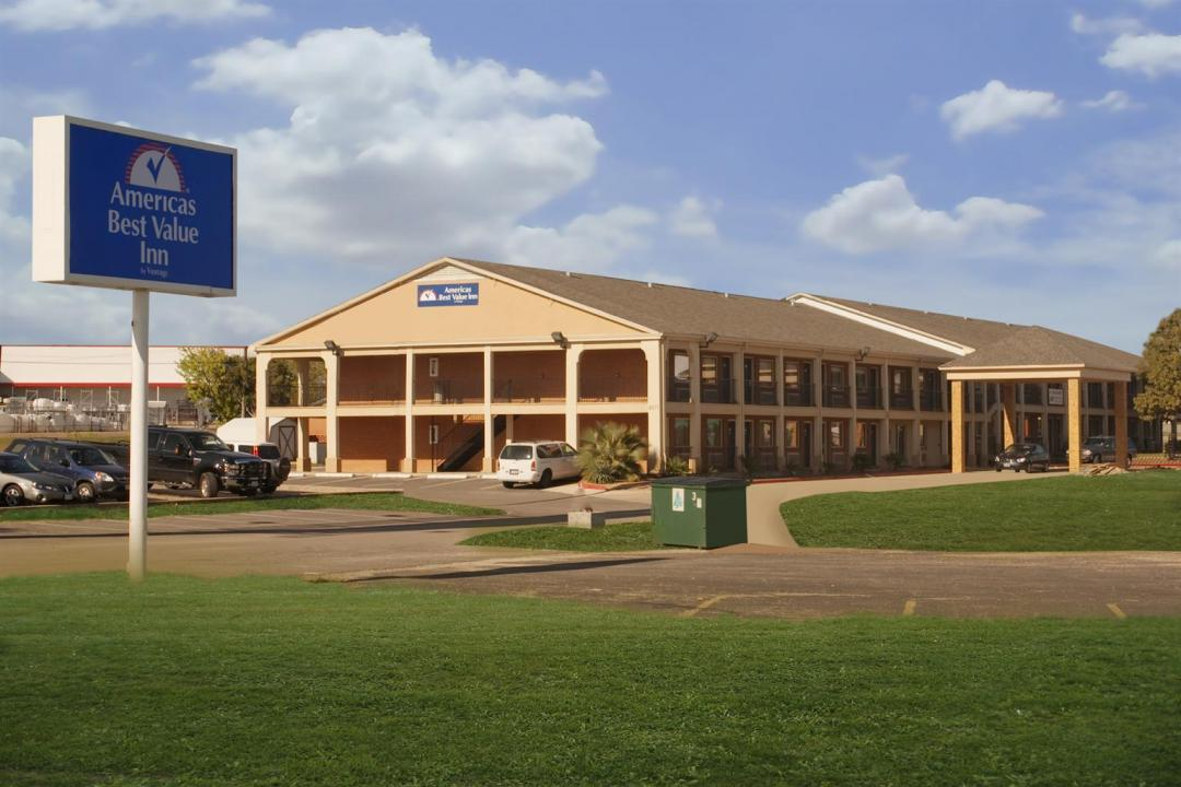 Street view of hotel exterior with parking, lawn, and sign