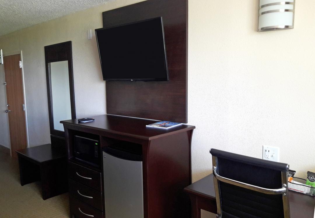 Side View of Flat Screen TV, Mirror, Desk and Chair, and Amenities