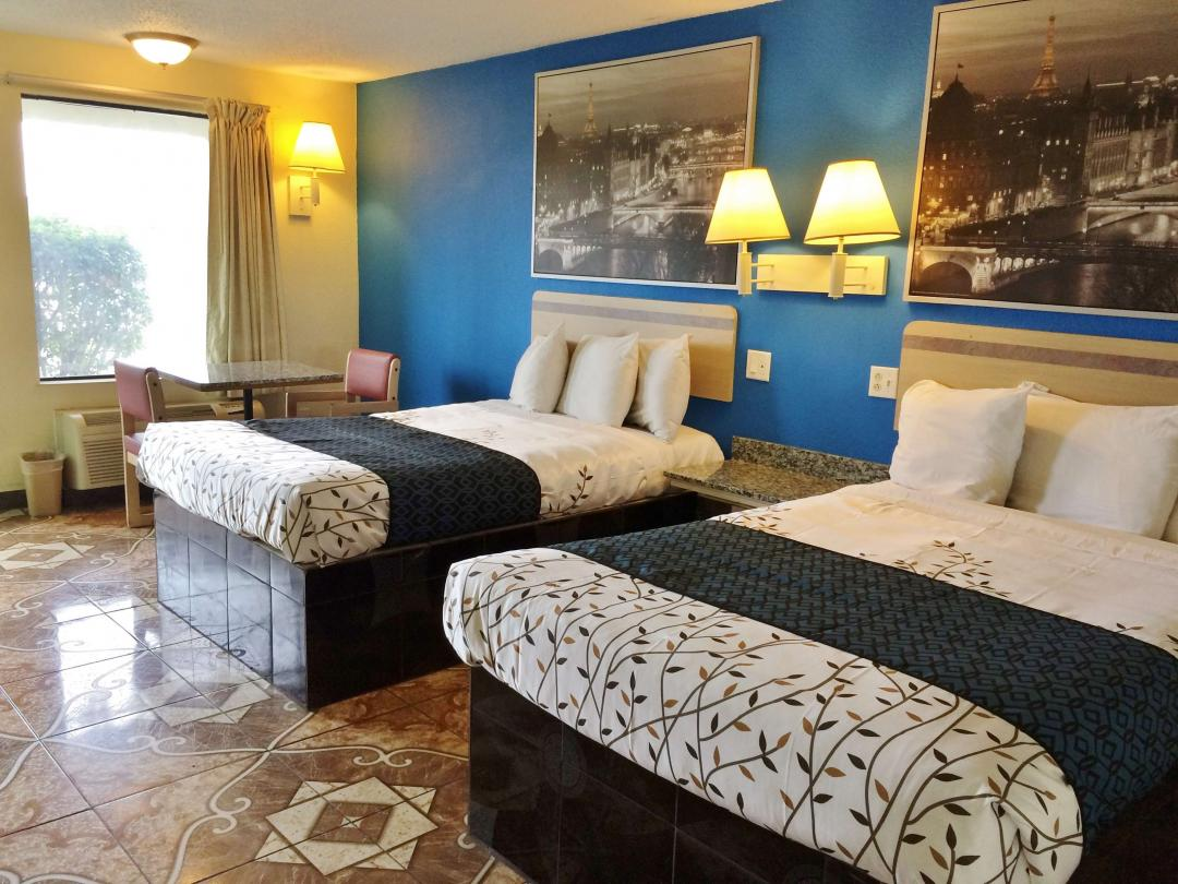 Guest room with two double beds and table with two chairs