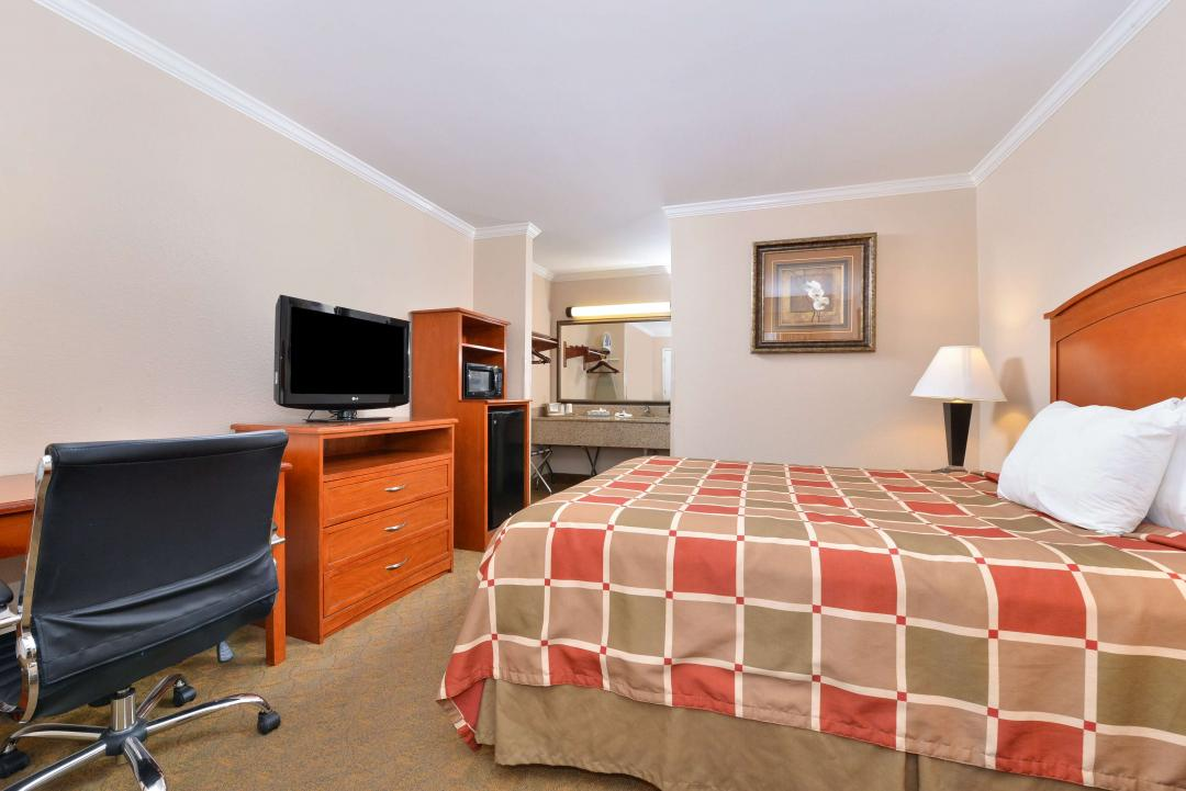 One King Bed with Desk, Flatscreen TV, Fridge, Microwave, and Vanity