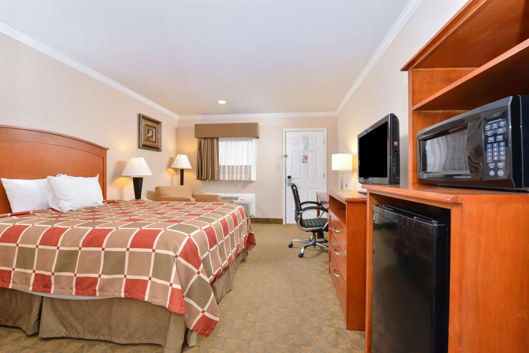 One King Bed with Flatscreen TV, Fridge, Microwave, and desk