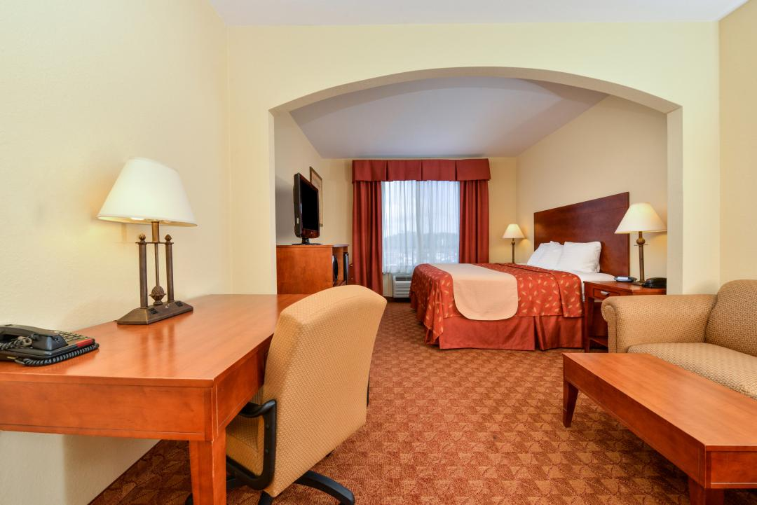 Spacious guest room with one king bed, sofa, table, desk and chair