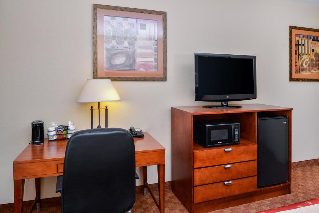 Room with desk, chair, flat screen tv, fridge and microwave