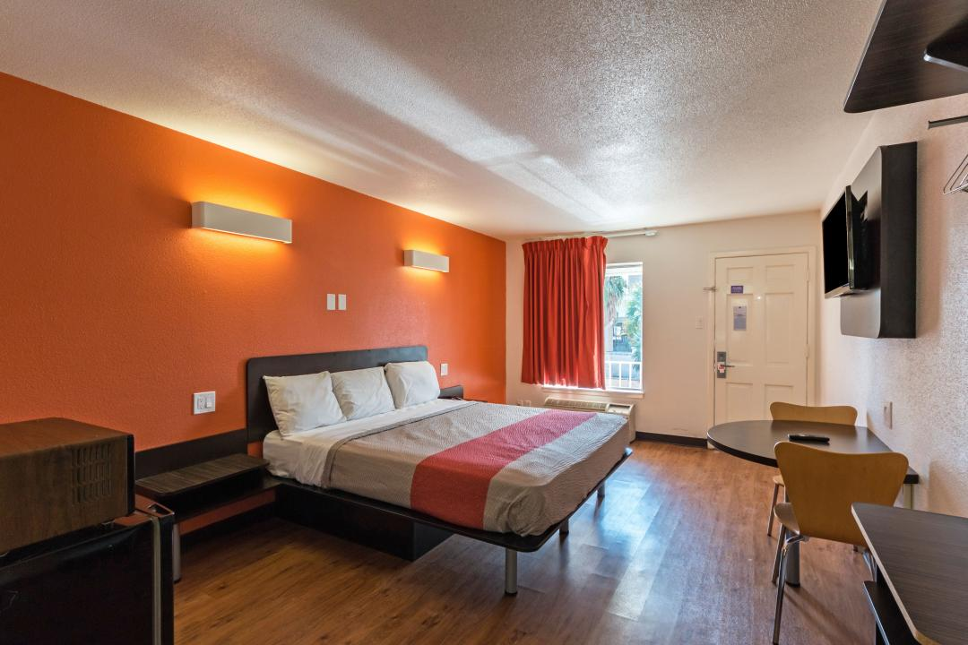 One kingbed room on hardwood floor with desk and chair