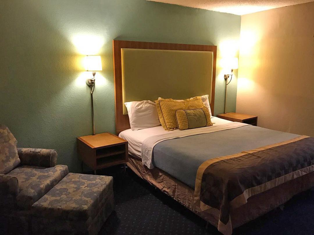 Guest room with on queen bed and lounge chair