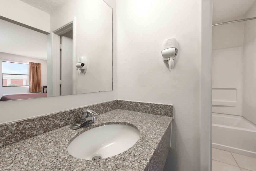 Clean and well lit guestroom bathrooms with hairdryer