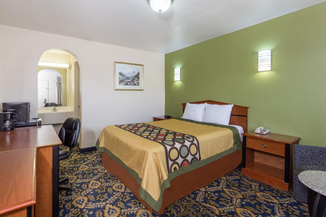 Nicely appointed guest room with one queen bed, desk, microwave and refrigerator